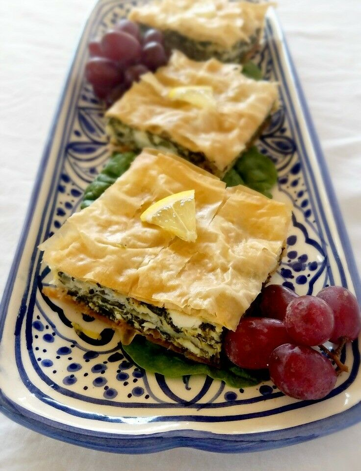Squares of spanakopita on a blue decorative tray.