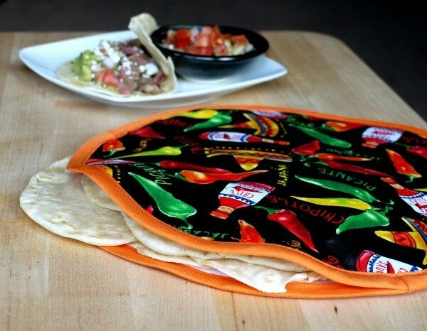 Colorful homemade fabric tortilla warmer filled with flour tortillas.